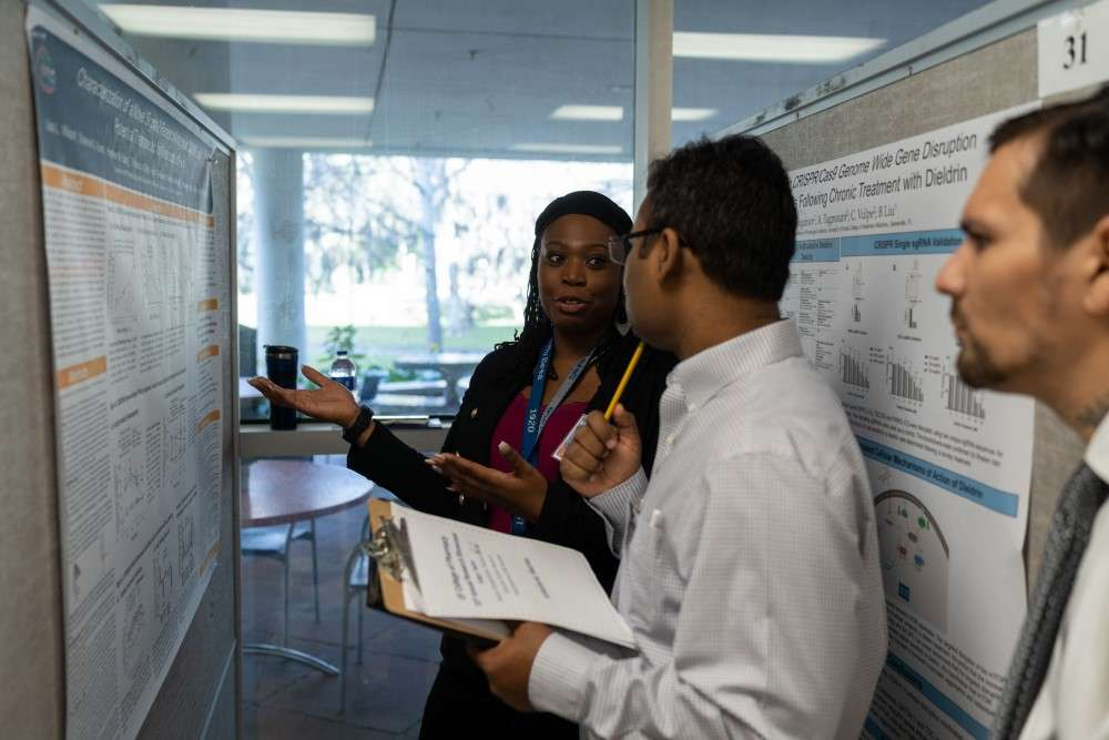 Student highlight aspects of her poster to the judges at the 2020 Research Showcase